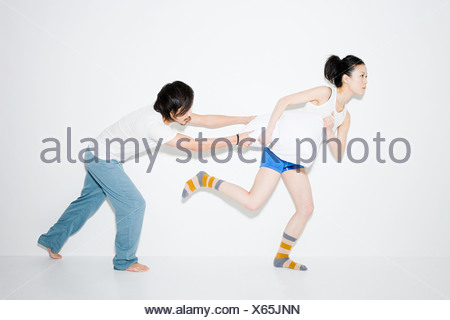 Couple fighting over pillow - Stock Photo