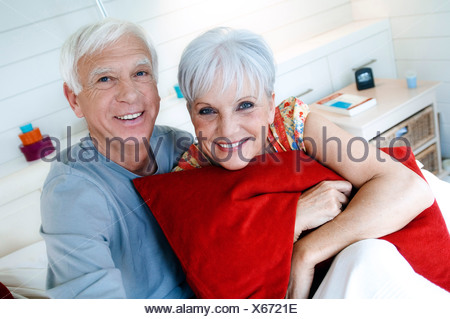 Senior couple sitting on a bed, smiling for the camera - Stock Photo