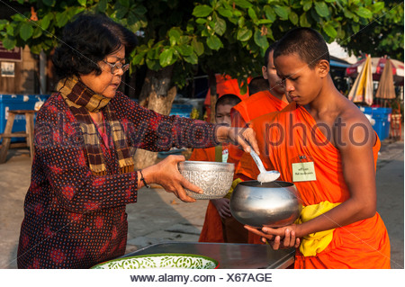 Morning alms round, a young Buddhist monk from a monastery school holding a begging bowl, receiving rice or offerings from an - Stock Photo