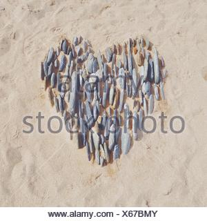 Heart in the sand made with pebbles - Stock Photo