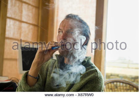 A man using an electronic cigarette, vaping. - Stock Photo