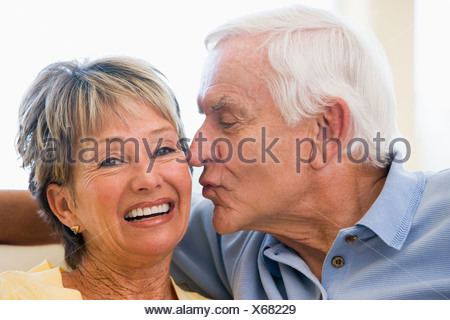 Couple relaxing in living room kissing and smiling - Stock Photo
