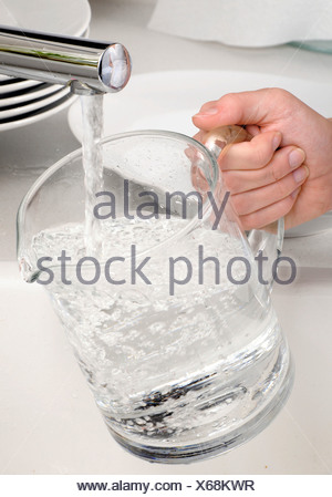 WOMAN FILLING JUG WITH TAP WATER - Stock Photo
