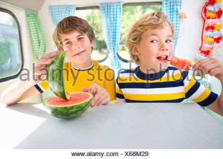 Boys eating watermelon in caravan, portrait - Stock Photo