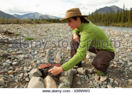 Young woman cooking on a camp fire, BBQ, grilling hamburger, gravel bar, Wind River, Yukon Territory, Canada - Stock Photo