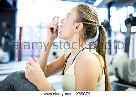 PROPERTY RELEASED. MODEL RELEASED. Young woman using inhaler in gym. - Stock Photo