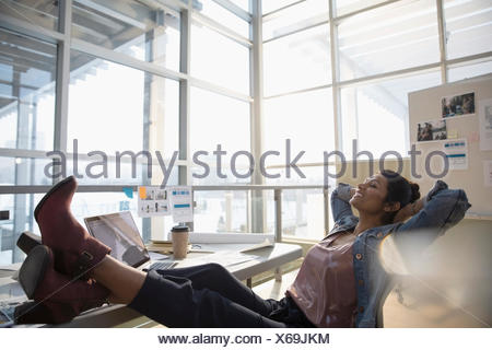 Confident female designer with feet up and hands behind head in office - Stock Photo