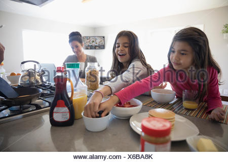 Smiling sisters eating breakfast in kitchen - Stock Photo