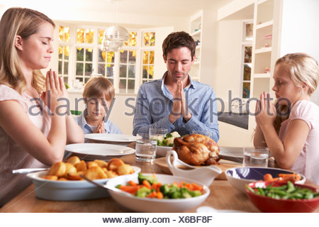 Family Saying Prayer Before Eating Roast Dinner - Stock Photo