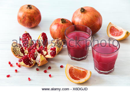 Pomegranate liqueur in a glasses on wooden table. Selective focus. - Stock Photo
