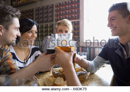Friends toasting beer glasses at brewery - Stock Photo