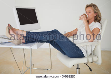 Casual businesswoman having a coffee with her feet up at desk - Stock Photo