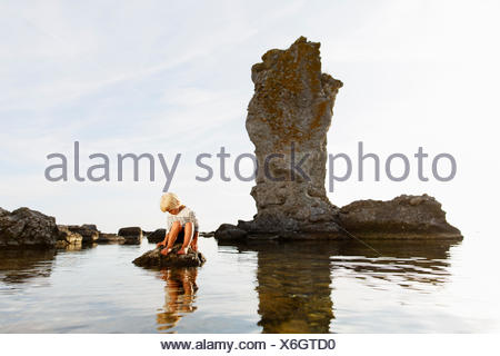 Sweden, Gotland, Faro, Blonde little boy (2-3) sitting on rock at Baltic Sea - Stock Photo