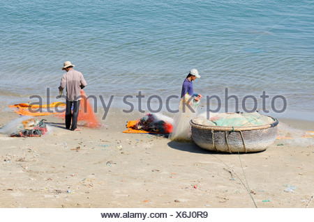 Two fishermen on a beach repairing their fishing nets, Mui Ne, Vietnam, Asia - Stock Photo