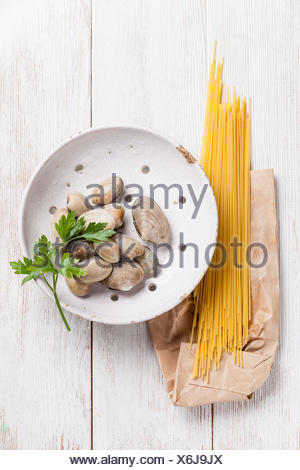 Raw shells vongole and raw sapaghetti for cooking pasta vongole on white wooden background - Stock Photo
