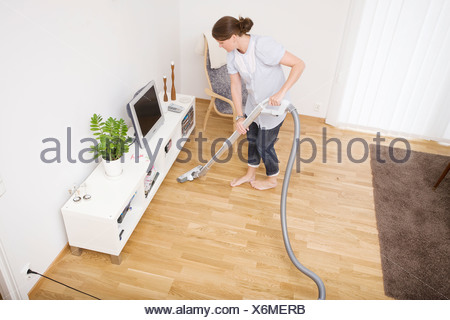 High angle view of a woman vacuuming the wooden floor at home - Stock Photo