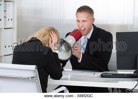 Boss Shouting At Businesswoman Through Loudspeaker In Office - Stock Photo