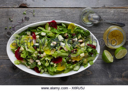 White ceramic bowl full of fresh mixed lettuce salad with healthy toppings, shot areal view with vinaigrette and limes beside th - Stock Photo