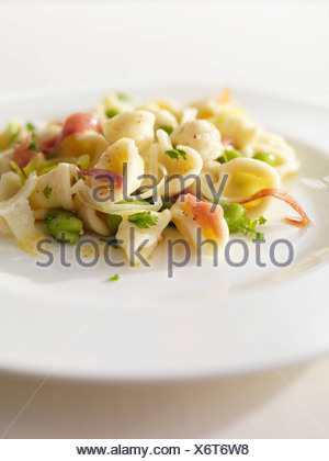 Orecchiette with raw ham and broad beans - Stock Photo