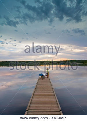 A couple, man and woman sitting at the end of a long wooden dock reaching out into a calm lake, at sunset. - Stock Photo