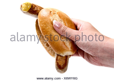 Hand holding a bratwurst sausage in a bun with mustard - Stock Photo