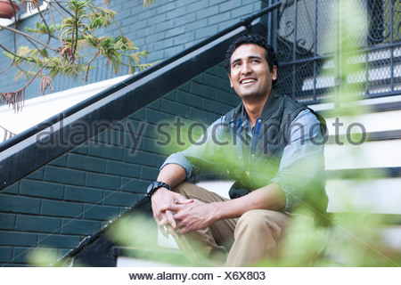 Portrait of young man sitting on steps - Stock Photo