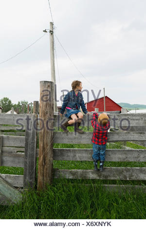 Brother and sister on fence in rural pasture - Stock Photo