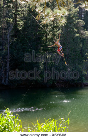 Boy 9 11 in swimming shorts letting go of rope swing above lake - Stock Photo