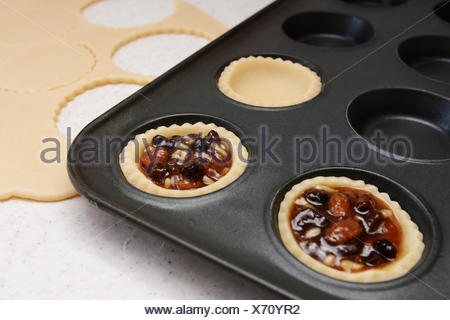 Making mince pies - pastry cases filled with traditional mincemeat - Stock Photo