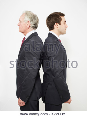 Businessmen standing back to back - Stock Photo