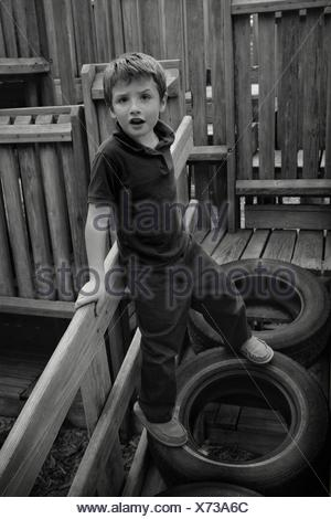 High Angle Portrait Of Boy Standing On Tire At Playground - Stock Photo