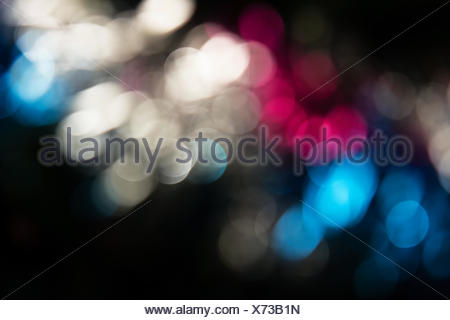Holiday abstraction. Multi-colored bright glare on dark background - Stock Photo