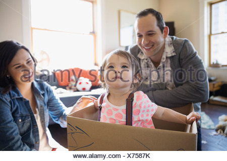 Baby girl playing inside of cardboard box - Stock Photo