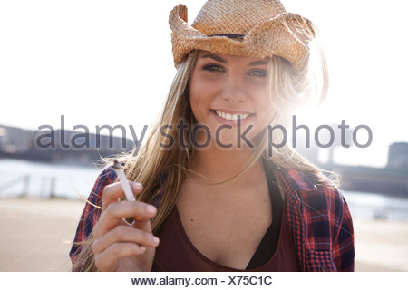 Portrait of smiling young woman wearing cowboy hat - Stock Photo