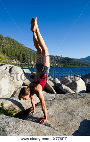 A young woman performs a handstand while doing yoga on granite boulders on the east shore of Lake Tahoe in the summer, NV. - Stock Photo