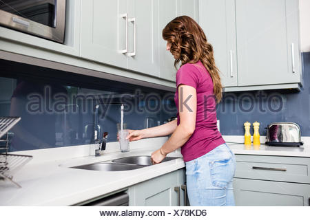 Woman filling water in glass from faucet - Stock Photo