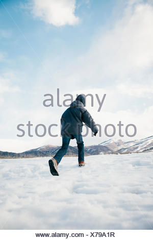 A boy running away across the snow. - Stock Photo