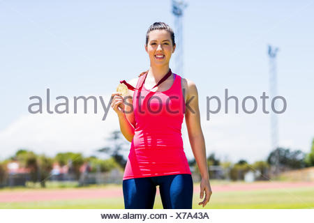 Portrait of female athlete showing her gold medal - Stock Photo