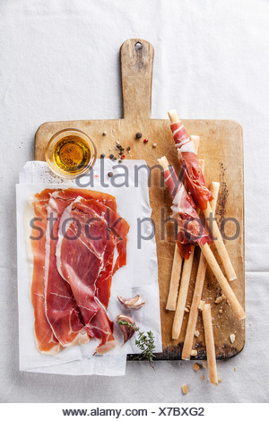 Bread sticks with ham on wooden cutting Board - Stock Photo