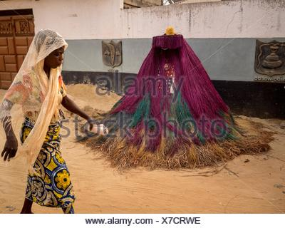 A woman walking in front of a Zangbeto mask, known as a 'Nightwatchman,' the traditional voodoo guardian of the night in the Yoruba religion of Benin and Togo. - Stock Photo