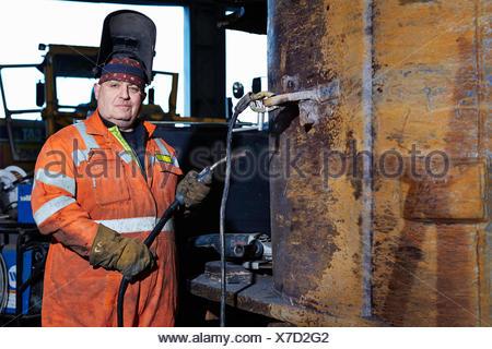 Portrait of mature welder in quarry workshop - Stock Photo