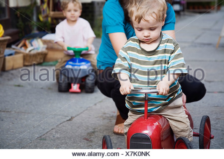 Germany, Berlin, Mother and boy (2-3) (3-4) on toy tractor, close-up - Stock Photo
