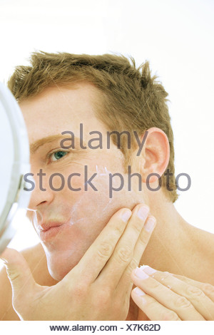 A man moisturizing his face - Stock Photo