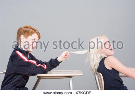 Boy pulling girl's hair - Stock Photo