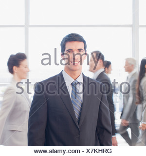 Busy co-workers walking past businessman - Stock Photo