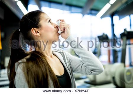 PROPERTY RELEASED. MODEL RELEASED. Close-up of young woman using inhaler in gym. - Stock Photo
