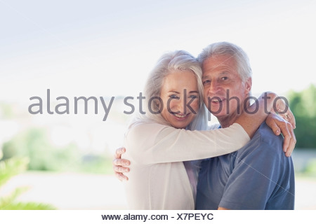 Older couple hugging outdoors - Stock Photo