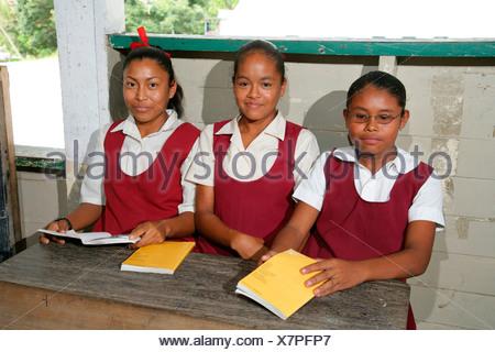 Schoolgirls in uniform during class, Amerindians, tribe of the Arawak, Kamuni river in the Guayana rainforest, South America - Stock Photo