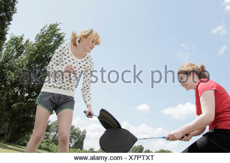Girls playing with rackets in park - Stock Photo