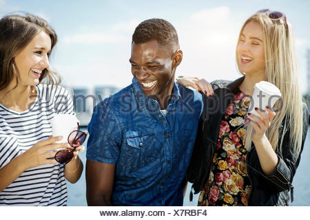 Germany, Duisburg, three young people having fun at Media Harbour - Stock Photo